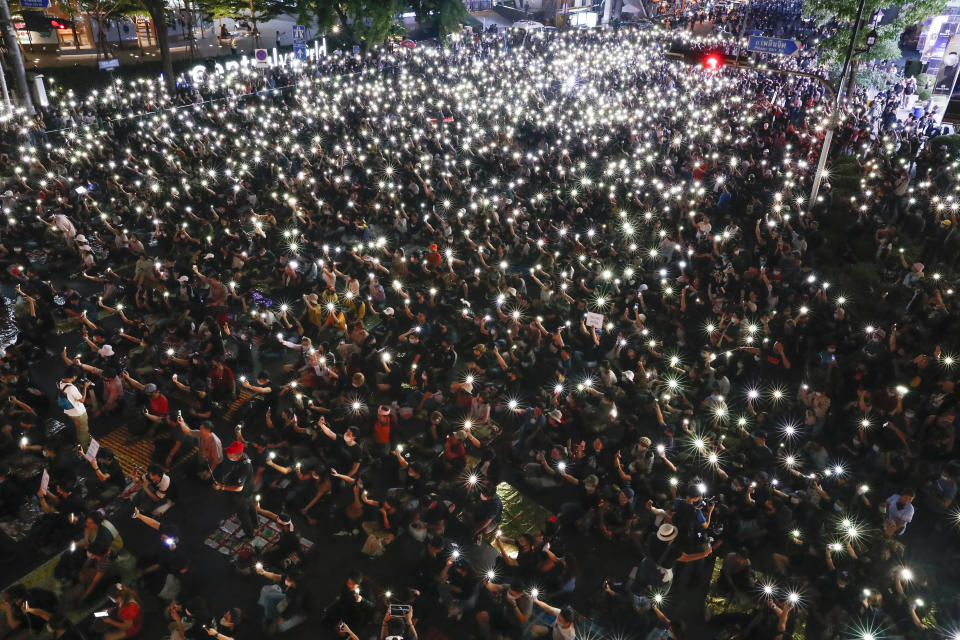 CORRECTS DATE Pro-democracy demonstrators shine their mobile phone lights during a march to the German Embassy in central Bangkok, Thailand, Sunday, Oct. 25, 2020. As lawmakers debated in a special session in Parliament that was called to address political tensions, student-led rallies were set to continue with a march through central Bangkok on Monday evening to the German Embassy, apparently to bring attention to the time King Maha Vajiralongkorn spends in Germany. (AP Photo/Gemunu Amarasinghe)