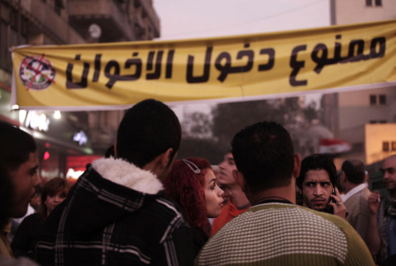 """Egyptians gather in front of a banner in Arabic that reads, """"members of the Muslim Brotherhood are not allowed,"""" during a demonstration in Tahrir Square, Cairo, Egypt, Friday, Nov. 30, 2012. Liberal and secular parties held major protests against Egyptian President Mohammed Morsi's latest decrees granting himself almost complete powers.(AP Photo/Nariman El-Mofty)"""