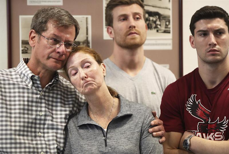 Parents John and Lisa Dombroski, left, stand with their sons John, behind, and Kevin during a press conference regarding their son and brother Mark: Blaire Simmons/The Royal Gazette via AP