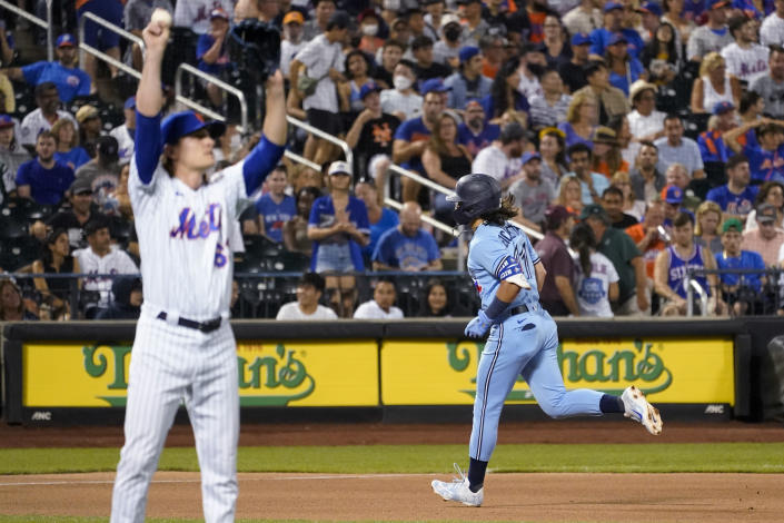 New York Mets relief pitcher Drew Smith, left, waits as Toronto Blue Jays' Bo Bichette runs the bases after hitting a home run during the seventh inning of a baseball game Saturday, July 24, 2021, in New York. (AP Photo/Mary Altaffer)