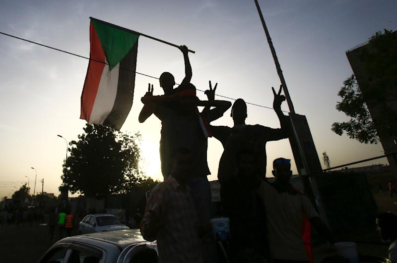 Sudanese protesters wave the national flag outside the military headquarters in the capital Khartoum on May 19, 2019 as talks were to resume between the military rulers and leaders of the demonstrators on a new governing body (AFP Photo/ASHRAF SHAZLY)