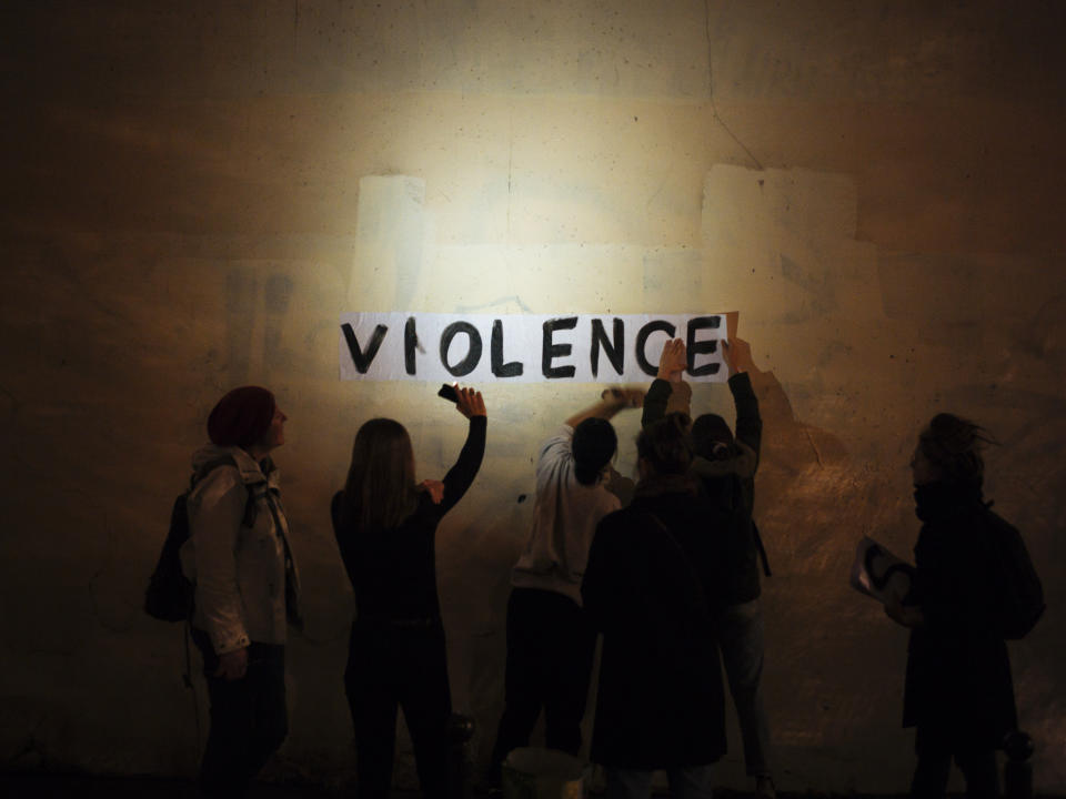 """The word """"violence"""" is pasted onto a wall by a group of women in a dark street in Paris. In Paris and cities across France, the signs are everywhere. """"Complaints ignored, women killed"""" and """"She leaves him, he kills her,"""" they read in black block letters pasted over stately municipal buildings. Under cover of night, activists have glued them to the walls to draw attention to domestic violence, a problem French President Emmanuel Macron has called """"France's shame."""" (Photo: Kamil Zihnioglu/AP)"""