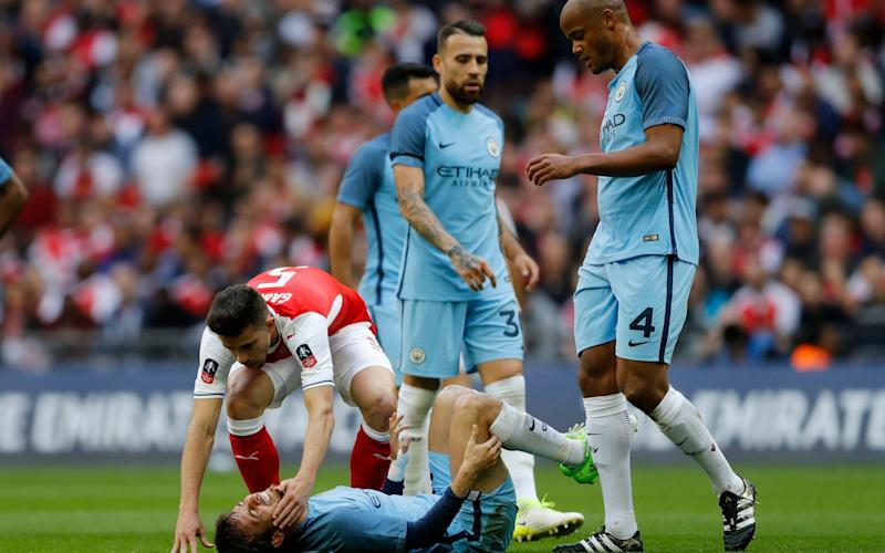 Manchester City's David Silva holds his leg after a challenge from Arsenal's Gabriel Paulista - Credit: Reuters