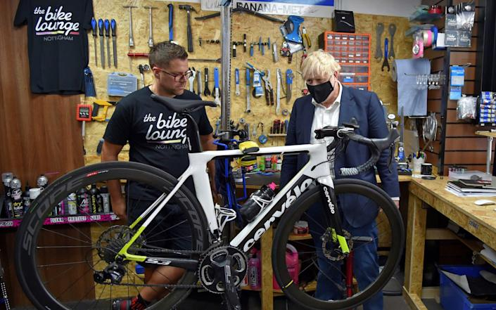 Britain's Prime Minister Boris Johnson wearing a face mask or covering due to the COVID-19 pandemic, talks to the owner of the the Cycle Lounge, Rodney Rouse, a bicycle repair shop in Beeston, central England, on July 28, 2020, during an event to launch the the government's new cycling intuitive to help get people fitter. - The British government promised Monday to build thousands of miles of new bike lanes to get people moving and healthy after months of coronavirus lockdown. Prime Minister Boris Johnson's pledge comes on the heels of a plan to force restaurants to display calories on menus as part of a broader effort to win the battle of the bulge. (Photo by Rui Vieira / POOL / AFP) (Photo by RUI VIEIRA/POOL/AFP via .) - AFP