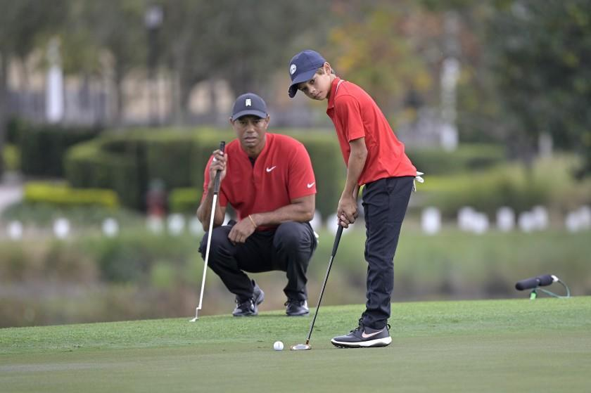 Tiger Woods watches his son Charlie putt on the 18th green during the final round of the PNC Championship golf tournament, Sunday, Dec. 20, 2020, in Orlando, Fla. (AP Photo/Phelan M. Ebenhack)