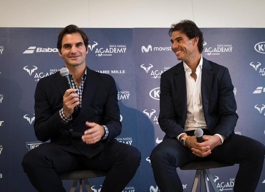 Spanish tennis player Rafael Nadal (R) smiles beside Swiss's player tennis Roger Federer during the opening of the Rafa Nadal Academy in Manacor on October 19, 2016. (AFP Photo/JAIME REINA)