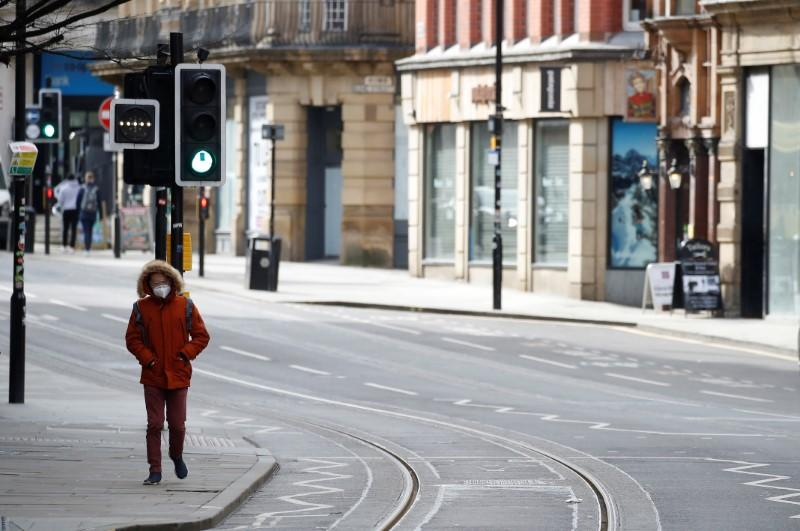 A man wears a mask as he walks along a deserted street amid the coronavirus outbreak in Manchester, Britain