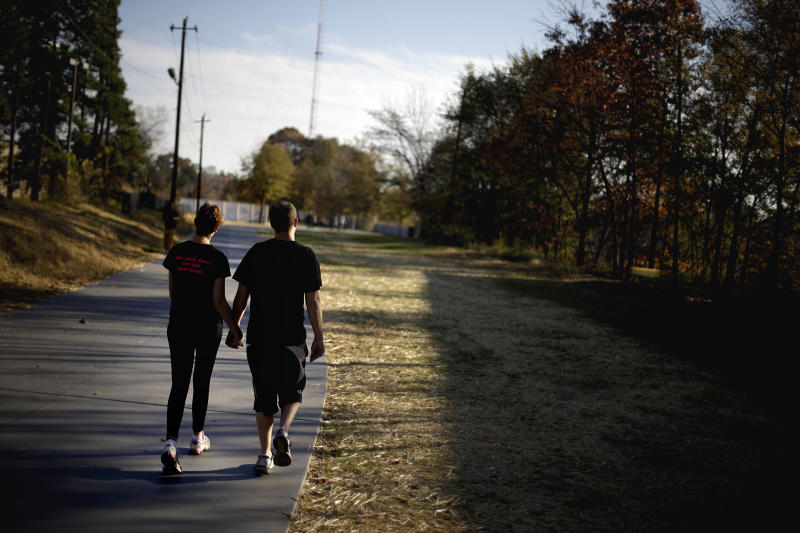 In this Nov. 20, 2012 photo, a couple walks along the Atlanta BeltLine in Atlanta. Since an Atlanta nonprofit opened a 2.25-mile-long paved trail east of downtown last month, it has attracted a steady stream of joggers, dog-walkers and cyclists to take in spectacular views of the skyline as well as a slice of established neighborhoods that were once only seen by riding a freight train. The Eastside Trail is the latest and most visible phase of the Atlanta BeltLine, an ambitious $2.8 billion plan to transform a 22-mile railroad corridor that encircles Atlanta into a network of parks, trails, public art, affordable homes and ultimately streetcars. (AP Photo/David Goldman)