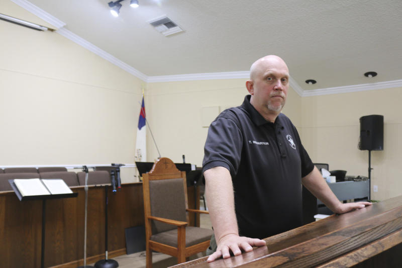 In this Oct. 17, 2019 photo, the Rev. Tommy Richardson, who serves as the chaplain for the sheriff's department, poses in Baker County, Fla. Richardson says his community is a forgiving place. Some Baker County residents express compassion for a teenager who wrote a school shooting plan and says he is in need of help. They are showing less mercy for a judge who released him without requiring mental health services, saying she failed their community and the boy she spared. (AP Photo/Bobby Caina Calvan)