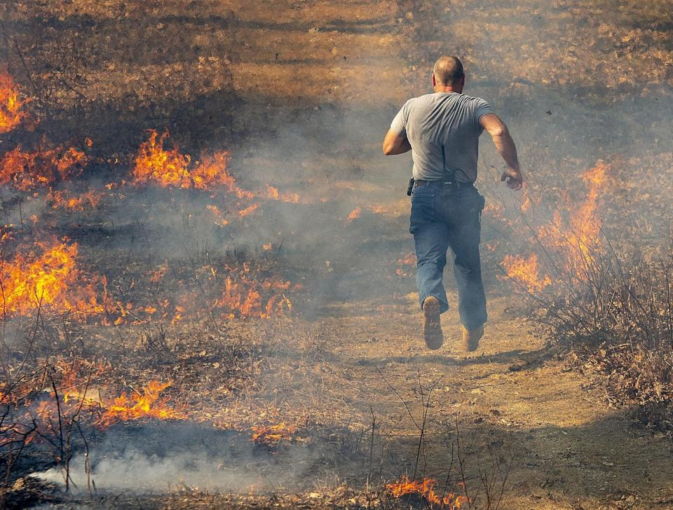 In 2020, Assistant Millbury Fire Chief Brian Gasco runs to save a hose from moving flames during a brush fire in Sutton, Massachusetts.