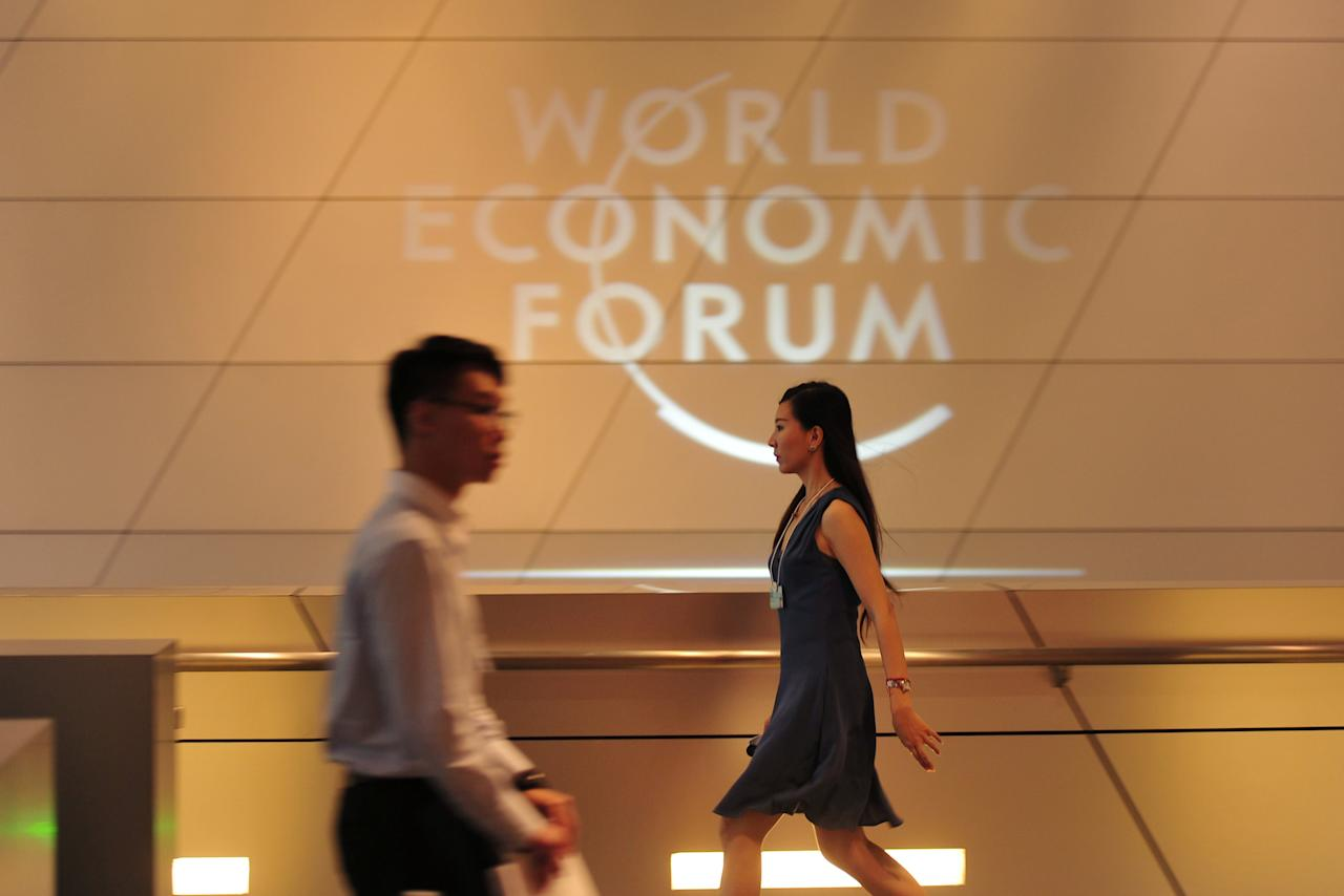 People walk past a logo at the World Economic Forum in Dalian, Liaoning province, China, June 27, 2017. Picture taken June 27, 2017. CNS/Yu Haiyang via REUTERS ATTENTION EDITORS - THIS IMAGE WAS PROVIDED BY A THIRD PARTY. CHINA OUT. NO COMMERCIAL OR EDITORIAL SALES IN CHINA.