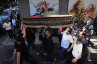 Mourners carry the coffin of Ibrahim Harb, 35, who was critically injured in the massive explosion at Beirut's port last year and who died on Monday nearly 14 months after the blast, as other throw rice during his funeral procession in Beirut, Lebanon, Tuesday, Sept. 28, 2021. On Aug. 4, 2020, hundreds of tons of ammonium nitrate, a highly explosive material used in fertilizers, ignited after a massive fire at the port. The death brings to at least 215 the number of people who have been killed by the blast, according to official records. (AP Photo/Hussein Malla)
