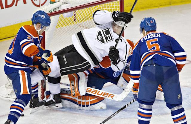Los Angeles Kings Dustin Brown, center, is pushed on top of Edmonton Oilers goalie Ben Scrivens ) by Andrew Ference, left, as Mark Fraser (5) looks on during second period NHL hockey action in Edmonton, Alberta, on Sunday March 9, 2014. (AP Photo/The Canadian Press, Jason Franson)