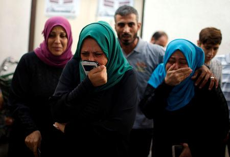 Relatives of a Palestinian, who was killed in an Israeli air strike, react at a hospital in the northern Gaza Strip October 17, 2018. REUTERS/Mohammed Salem