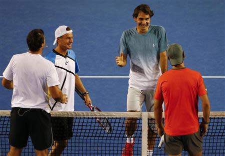 Federer smiles as he goes to shake hands with Nadal, as Hewitt and compatriot Rafter shake hands during the Kids Tennis Day before the Australian Open 2014 tennis tournament in Melbourne