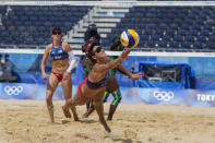 Sarah Sponcil, right, of the United States, dives for the ball as teammate Kelly Claes looks on during a women's beach volleyball match against Kenya at the 2020 Summer Olympics, Thursday, July 29, 2021, in Tokyo, Japan. (AP Photo/Petros Giannakouris)