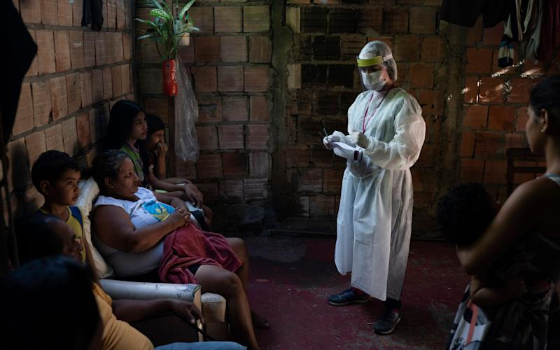A health worker give instructions to members of Da Costa family after some of them tested positive for COVID-19 in Manacapuru, Amazonas state, Brazil - AP