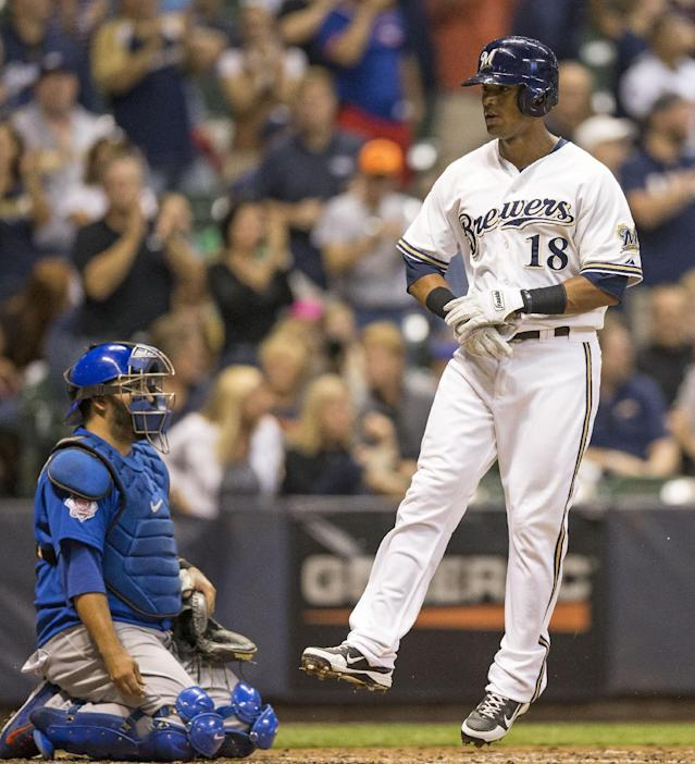 Milwaukee Brewers' Khris Davis leaps across home after hitting a solo home run during the fourth inning of a baseball game against the Chicago Cubs, Wednesday, Sept. 18, 2013, in Milwaukee. (AP Photo/Tom Lynn)