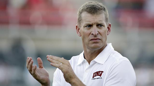 FILE - In this Sept. 6, 2014, file photo, UNLV head coach Bobby Hauck watches his team warm up before an NCAA football game against the Northern Colorado in Las Vegas. Hauck is back as the football coach at Montana, a program he led to three FCS national championship games. The university said in a statement Friday, Dec. 1, 2017, that Hauck agreed to a three-year contract taking him through the 2020 season. Other terms were not immediately released.(AP Photo/John Locher, File)