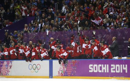 Canada players on the bench celebrate after their team defeated Team USA in their men's ice hockey semi-final game at the 2014 Sochi Winter Olympic Games, February 21, 2014. REUTERS/Jim Young