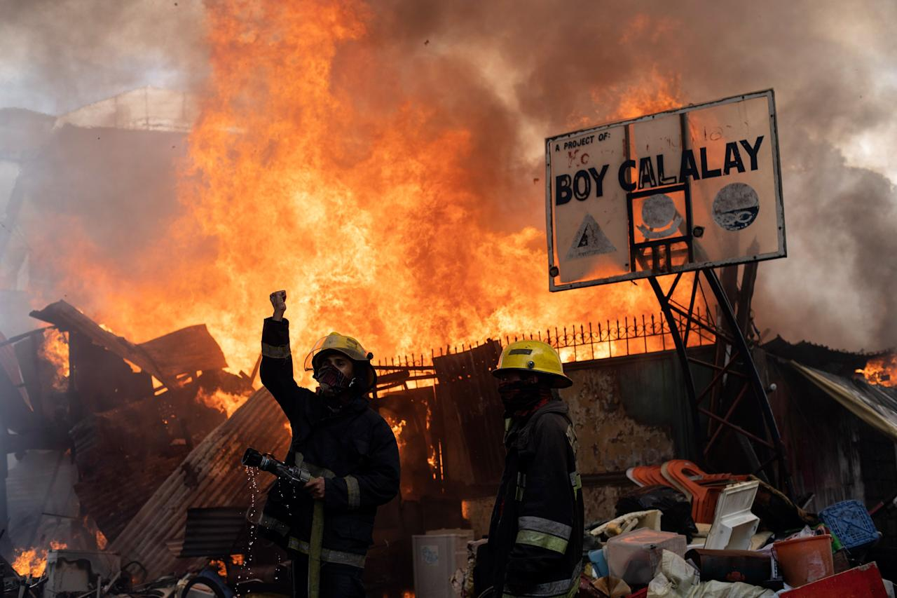 <p>Firefighters attempt to extinguish a fire that razed through a residential area in Manila on March 5, 2019. – About 150 houses were destroyed in the fire, leaving 400 families homeless, according to authorities. (Photo credit: NOEL CELIS/AFP/Getty Images) </p>