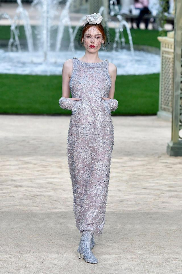 <p>Model wears a long, sleeveless, silver crystal-embellished gown from the Chanel SS18 Haute Couture show. (Photo: Getty Images) </p>