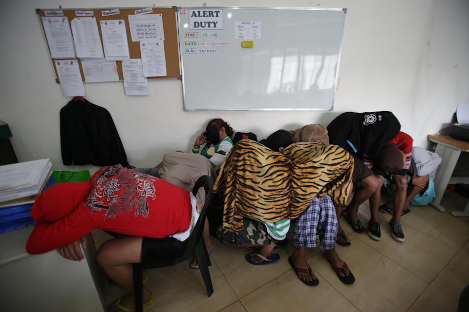 Suspects in an alleged Internet porn operation cover their faces as they stay at the Cybercrime Division of the National Bureau of Investigation in Manila, Philippines on Tuesday, Feb. 18, 2014. Philippine government agents have raided an alleged Internet child porn operation based in a school and arrested its president and eight other people, National Bureau of Investigation officials said. (AP Photo/Aaron Favila)