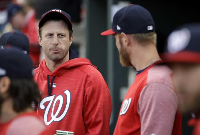 Washington Nationals pitcher Max Scherzer (left) chats with teammate Stephen Strasburg in the dugout during a game in 2017. (AP)