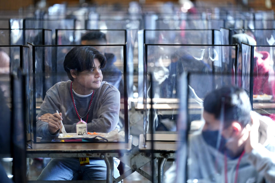 FILE - In this March 21, 2021, file photo, students sit separated by plastic dividers during lunch at Wyandotte County High School in Kansas City, Kan., on the first day of in-person learning. Children are having their noses swabbed or saliva sampled at school to test for the coronavirus in cities. As more children return to school buildings this spring, widely varying approaches have emerged on how and whether to test students and staff members for the virus. (AP Photo/Charlie Riedel, File)