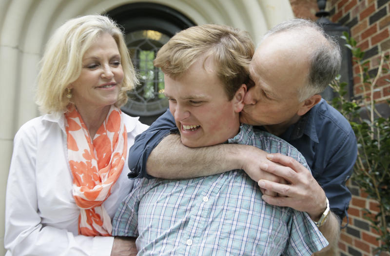 In this photo made Saturday, April 1, 2017, Clay Heighten, right, and Debra Caudy, left, embrace their autistic 19-year-old son Jon Heighten as they pose for a photo at their home in the Dallas area town of University Park, Texas. Jon Heighten's parents are helping lead a 29-acre housing development and community for autistic adults that will break ground in the coming months. (AP Photo/LM Otero)