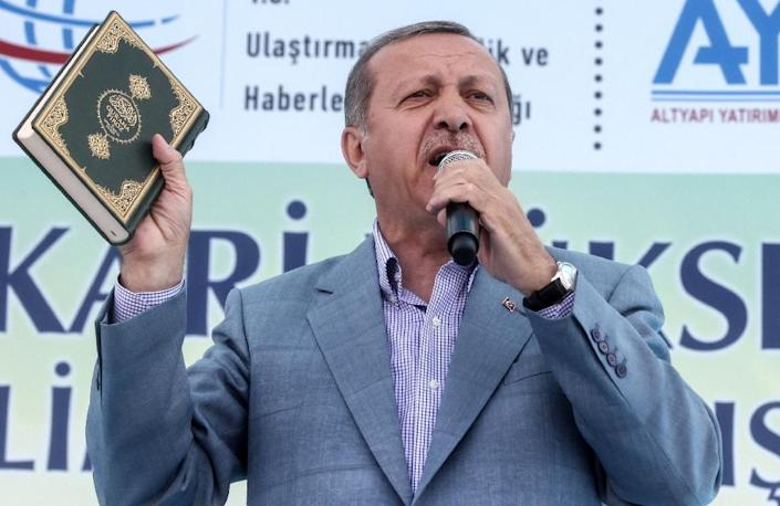 Turkish President Recep Tayyip Erdogan holds a Koran as he speaks during the opening ceremony of the Selehaddin Eyyubi airport in the eastern city of Hakkari, on May 26, 2015 (AFP Photo/)