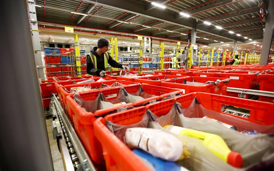 An employee loads customer orders onto a trolley at the Ocado Group Plc distribution centre in Dordon, North Warwickshire - Chris Ratcliffe/Bloomberg
