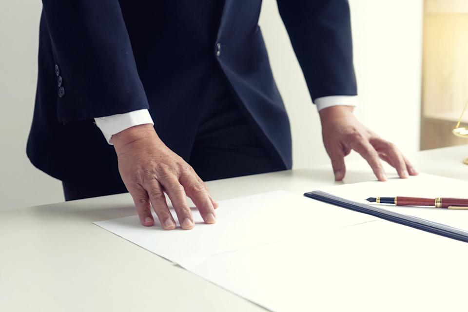 Businessman standing with his hands on a desk