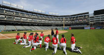 Players take a knee to listen to coaches before a baseball game in Arlington, Texas, Friday, March 8, 2019. More than 60 high school girls from the United States, as well as Canada and Puerto Rico are taking part in the inaugural MLB Grit event, a tournament specifically for girls who play baseball. (AP Photo/LM Otero)