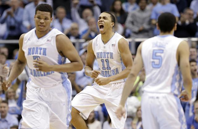 North Carolina's Brice Johnson (11) reacts following a basket against Syracuse during the second half of an NCAA college basketball game in Chapel Hill, N.C., Monday, Jan. 26, 2015. North Carolina won 93-83. Kennedy Meeks, left, and Marcus Paige (5) run up court. (AP Photo/Gerry Broome)