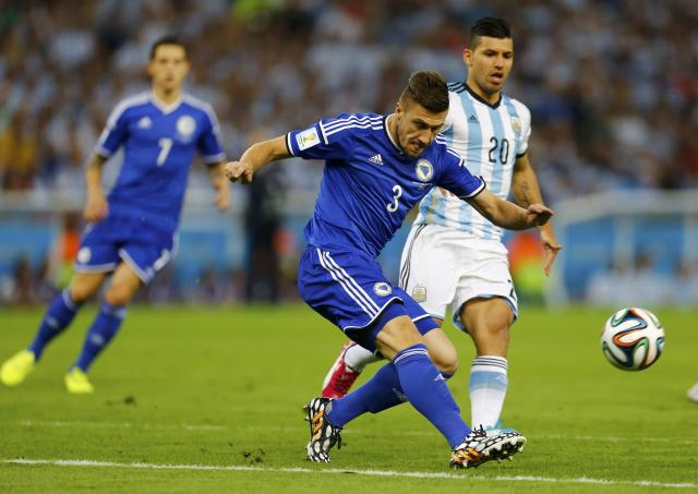 Bosnia's Ermin Bicakcic (C) clears the ball away from Argentina's Sergio Aguero during their 2014 World Cup Group F soccer match at the Maracana stadium in Rio de Janeiro June 15, 2014. REUTERS/Pilar Olivares (BRAZIL - Tags: SOCCER SPORT WORLD CUP)
