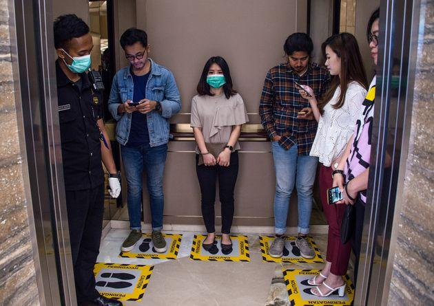 People stand on designated areas to ensure social distancing inside an elevator at a shopping mall in Surabaya, Indonesia. This is actually closer contact than the Centers for Disease Control and Prevention recommends.