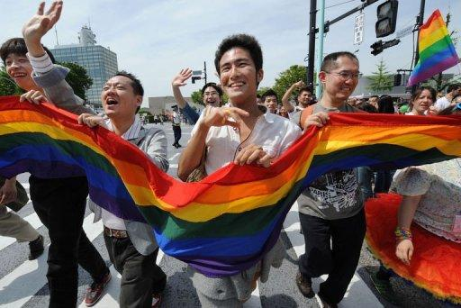 Gay people carry a rainbow flag as they march on the street during the Tokyo Rainbow Pride 2012