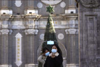 Visitors pose for a selfie outside the Wangfujing Church in Beijing on Friday, Dec. 25, 2020. Official churches in the Chinese capital abruptly cancelled mass on Christmas day in a last-minute move owing to the pandemic. The capital city is on high alert after new confirmed COVID-19 cases were reported last week and new asymptomatic cases reported Christmas day. (AP Photo/Ng Han Guan)