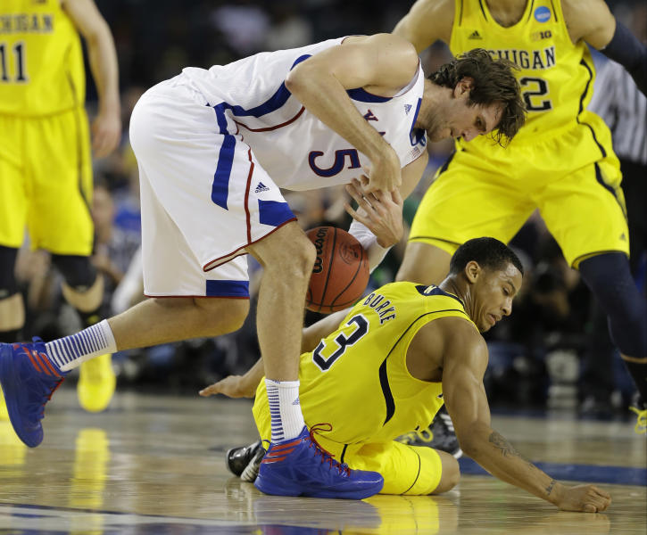 Kansas' Jeff Withey (5) and Michigan's Trey Burke (3) go after a loose ball during the first half of a regional semifinal game in the NCAA college basketball tournament, Friday, March 29, 2013, in Arlington, Texas. (AP Photo/Tony Gutierrez)
