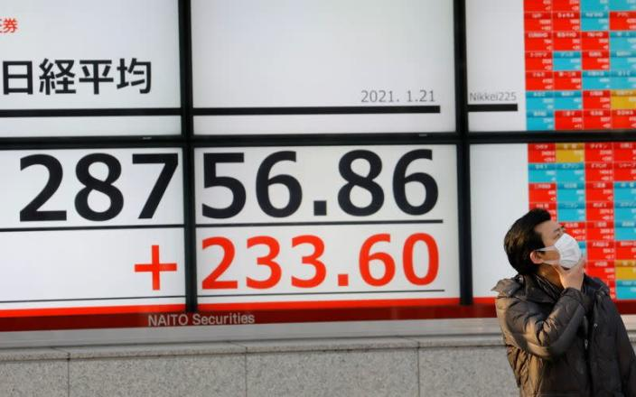 A man wearing a protective mask, amid the coronavirus disease (COVID-19) outbreak, stands in front of an electric board showing Nikkei index outside a brokerage in Tokyo