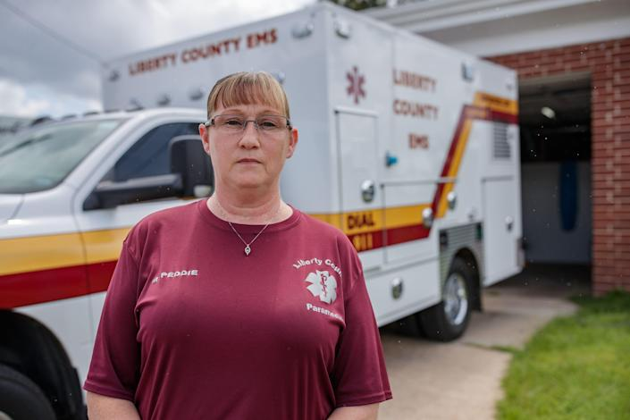 Melissa Peddie, Liberty County, director of emergency medical services in Liberty County, Florida, stands in front of the county's only active ambulance to transport patients Wednesday, July 21, 2021.