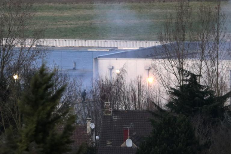 Police officers launch an assault as smoke rises from a building in Dammartin-en-Goele, northeast of Paris