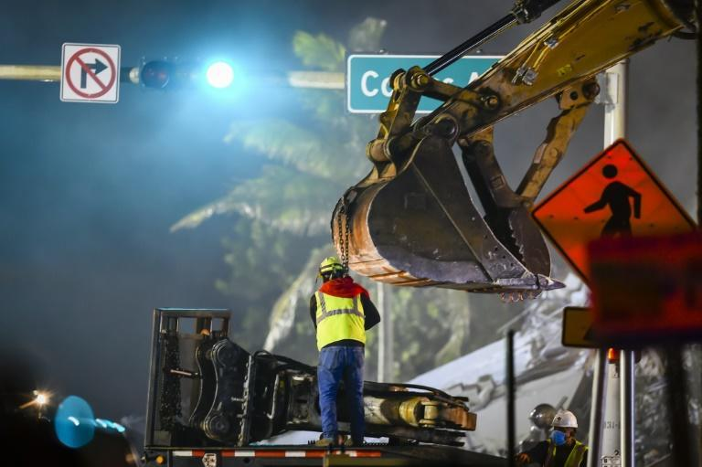 Rescue teams at work on the site of a partially collapsed building in Surfside, north of Miami Beach on June 25, 2021