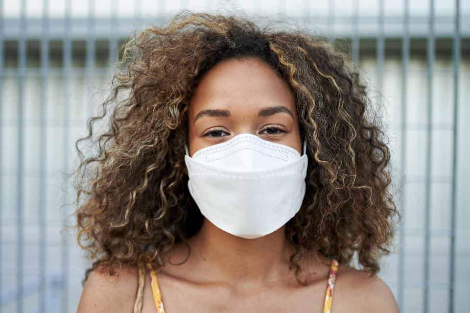 Portrait of young woman with antiviral mask outdoors
