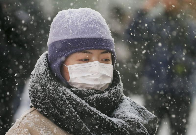 A woman walks with a face mask during a snow storm in Times Square in the Manhattan borough of New York, January 23, 2016. (Photo: REUTERS/Carlo Allegri)