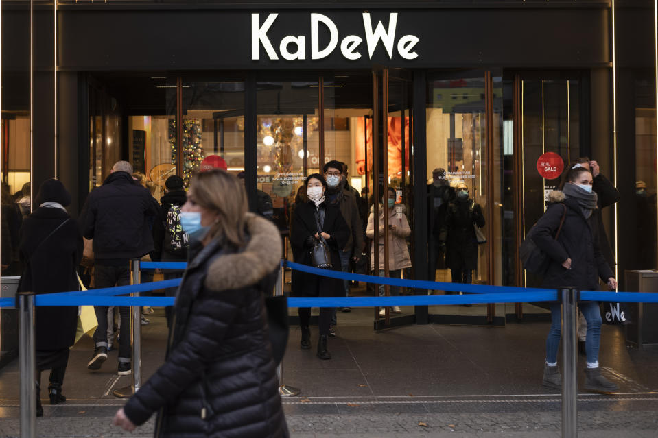 Customers enter and leave the KaDeWe department store a day before new restrictions begin in Berlin, Germany, Tuesday, Dec. 15, 2020. Chancellor Angela Merkel and the governors of Germany's 16 states agreed Sunday to step up the country's lockdown measures beginning Wednesday and running to Jan. 10 to stop the exponential rise of COVID-19 cases. (AP Photo/Markus Schreiber)