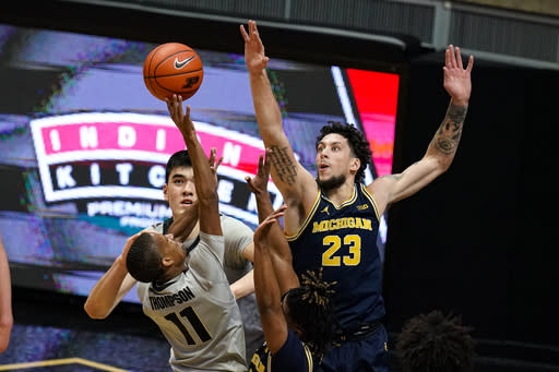 Michigan forward Brandon Johns Jr. (23) goes up to block the shot of Purdue guard Isaiah Thompson (11) during the first half of an NCAA college basketball game in West Lafayette, Ind., Friday, Jan. 22, 2021. (AP Photo/Michael Conroy)