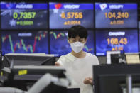 A currency trader watches monitors at the foreign exchange dealing room of the KEB Hana Bank headquarters in Seoul, South Korea, Friday, Nov. 27, 2020. Asian stock markets declined Friday as questions about the effectiveness of one possible coronavirus vaccine weighed on investor optimism. (AP Photo/Ahn Young-joon)