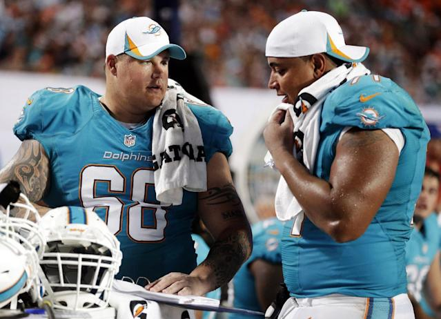 """FILE - In this Aug. 24, 2013, file photo, Miami Dolphins guard Richie Incognito (68) and tackle Jonathan Martin (71) look over plays during an NFL preseason football game against the Tampa Bay Buccaneers in Miami Gardens, Fla. Martin was subjected to """"a pattern of harassment"""" that included racist slurs and vicious sexual taunts about his mother and sister by three teammates, according to a report ordered by the NFL. The report said Incognito, who was suspended by the Dolphins in November, and fellow offensive linemen John Jerry and Mike Pouncey harassed Martin. (AP Photo/Wilfredo Lee, File)"""